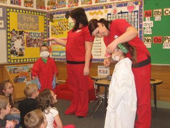 dental team teaching children dressed as dentists