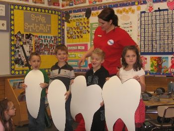 hygienist teaching young children holding cutout paper teeth