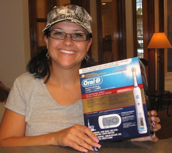 smiling woman wearing hat and glasses holding toothbrush