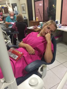 young woman in pink scrubs laying in dental chair