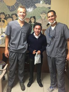 dentist and assistant smiling with patient