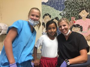 dentist and assistant smiling with young patient