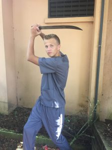 blonde teenager wearing grey scrubs holding a machete