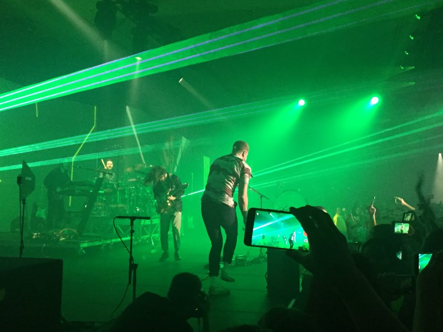 image of a band performing on stage with green lights
